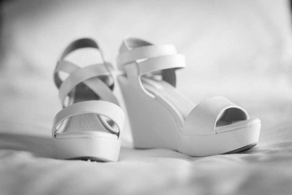The brides white shoes lit by window. Definitely chosen to be able to walk on the sand!