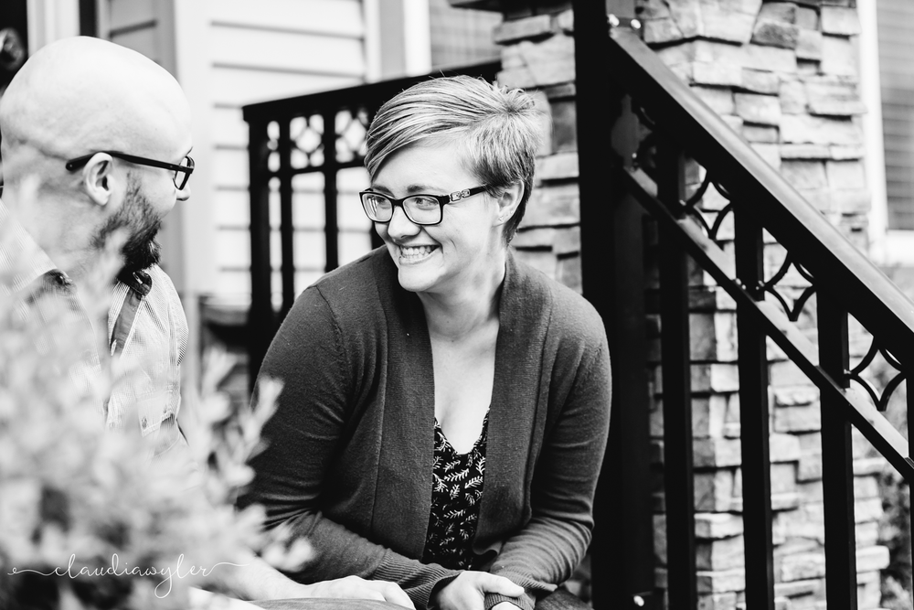 Couple sitting on front door step laughing.