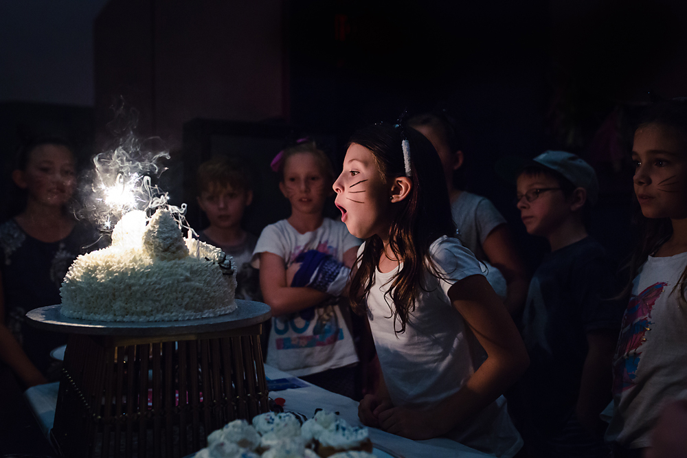 Young girl blowing out her birthday candles on her cat cake in dark room surrounded by her friends.
