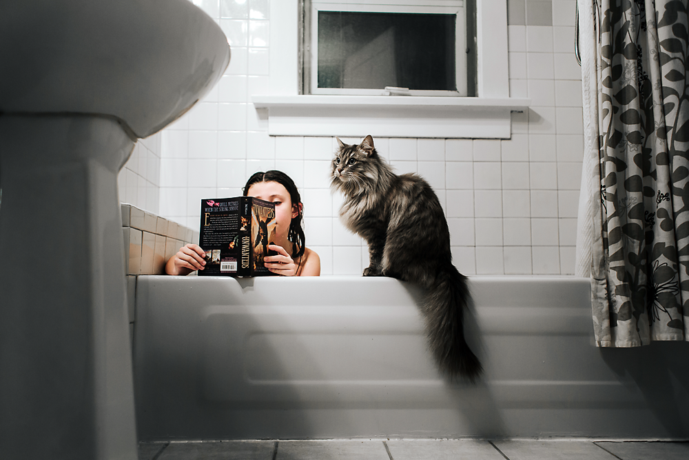 Young girl reading her book in the bath tub with her cat watching on edge.