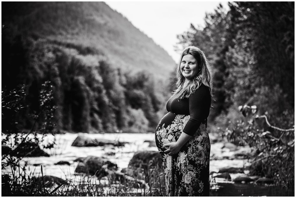 Pregnant women standing in Vedder River in flowing maternity dress.