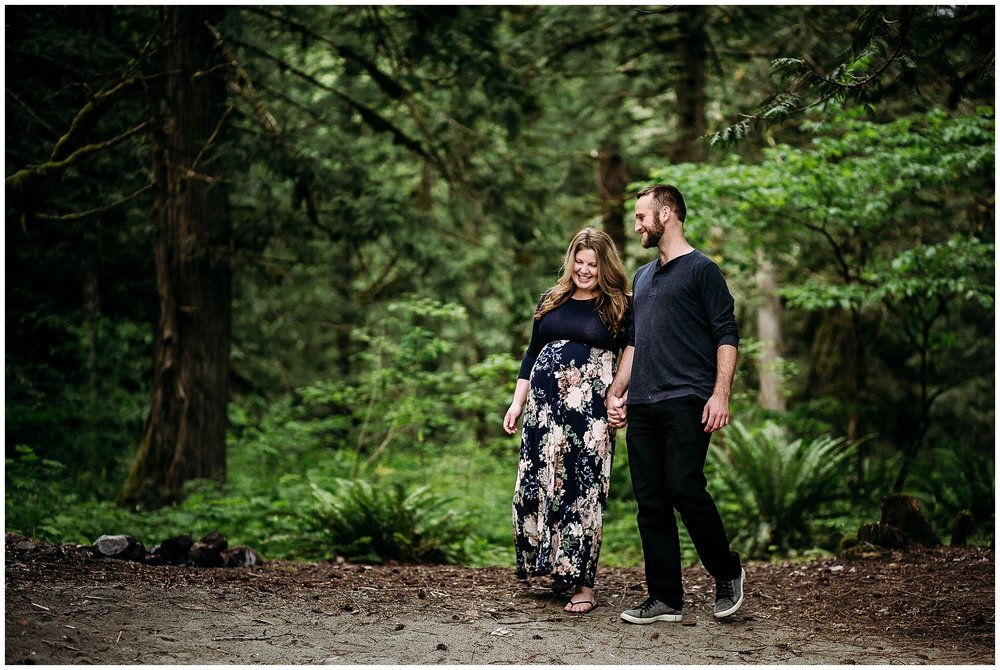 Pregnant Chilliwack, BC woman walking through the Pacific Northwest forest with her husband in a long flowing floral dress.