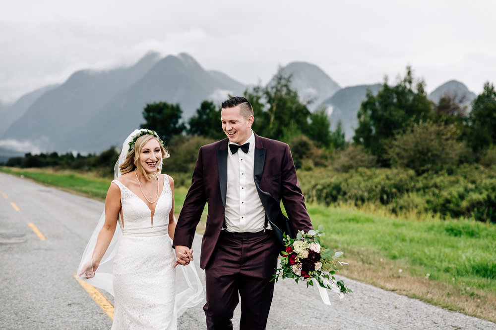 Bride and Groom walking down empty street holding wedding boquet with storm clouds and mountains in the distance.