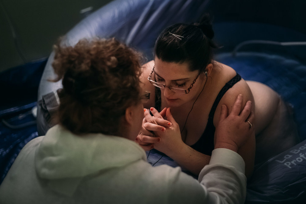 Mother praying with her doula during her labour in birthing pool