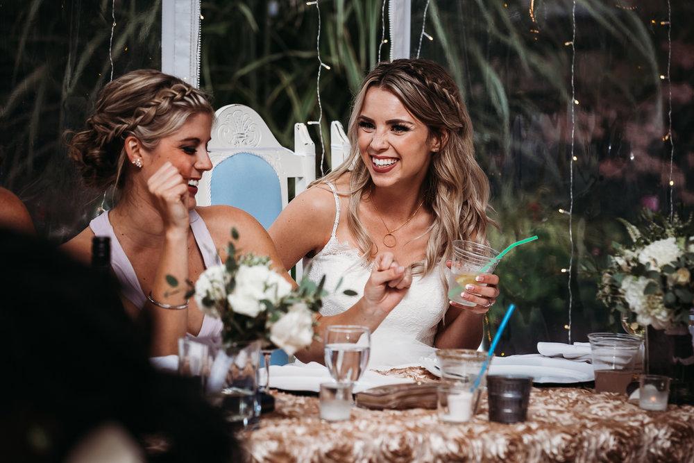Bride and Bridesmaid sharing a laugh at head table during wedding reception