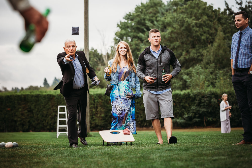 Father of the Groom playing bean bag toss at outdoor wedding in Fraser Valley, BC