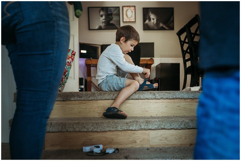 boy putting on shoes at door step