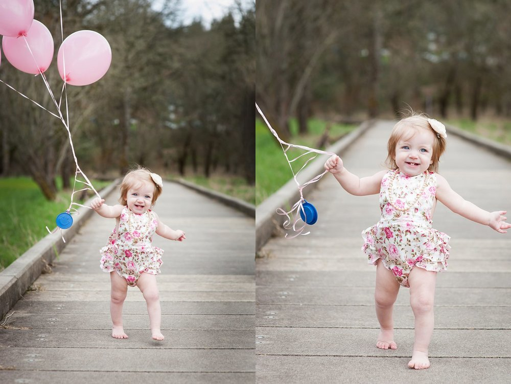 1 year old girl running with her birthday balloons