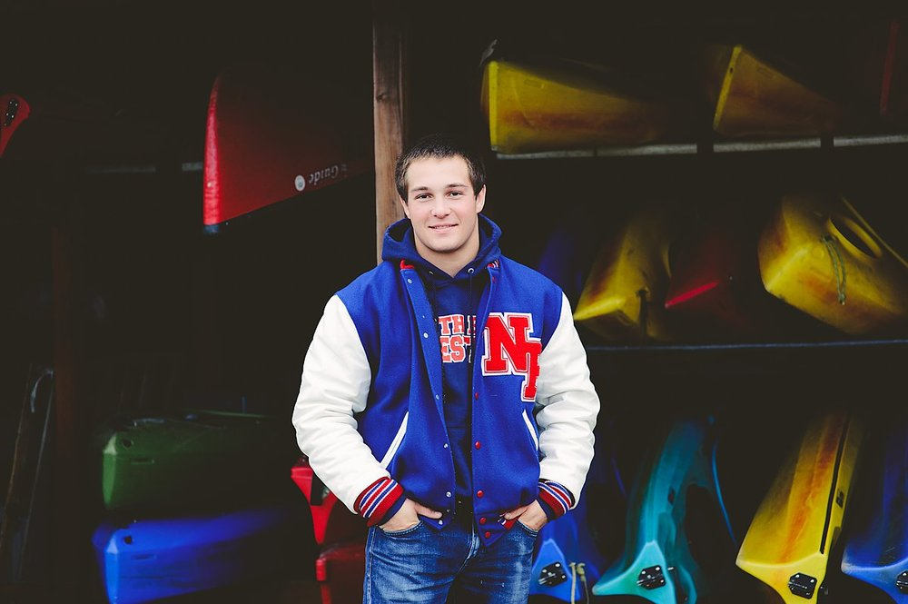 Senior Boy in Lettermen's Jacket, colorful photo with canoes, a vibrant Senior Experience Photoshoot.