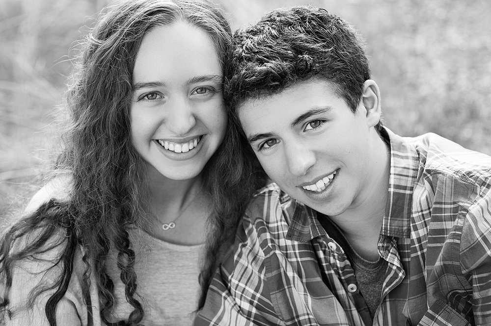 black and white photos of older siblings, infinity necklace and natural smiles.