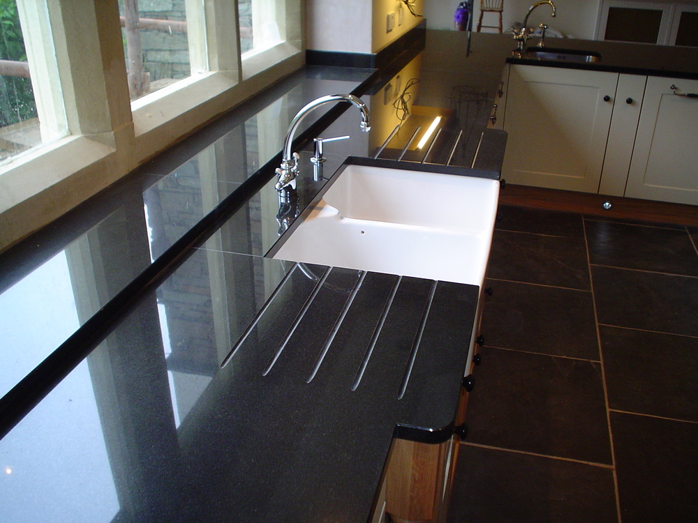 black-granite-worktop-with-belfast-sink-double-drainer-break-front.jpg
