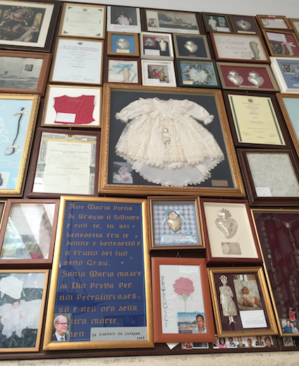 Fig. 1: Baby's baptismal outfit and other votives seen in the Sanctuary of the Blessed Madonna of the Rosary of Pompeii, April 2016. Photo by author.