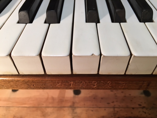 The old, chipped and worn ivories, prior to new key coverings including new solid ebony sharps
