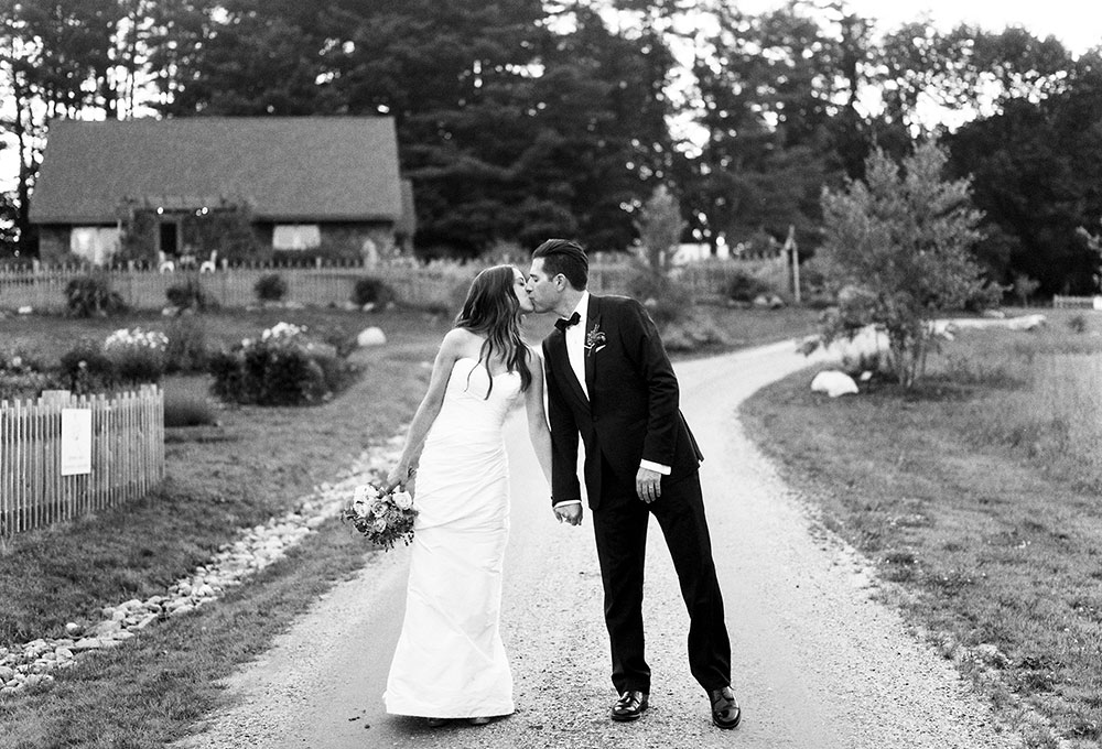 black and white film wedding photo of bride and groom kissing