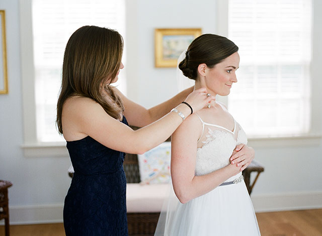 maid of honor helps bride put on her necklace - Sarah Der Photography