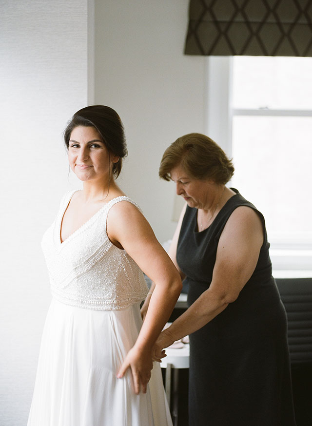 elegant image of mother zipping bride into her wedding gown - Sarah Der Photography