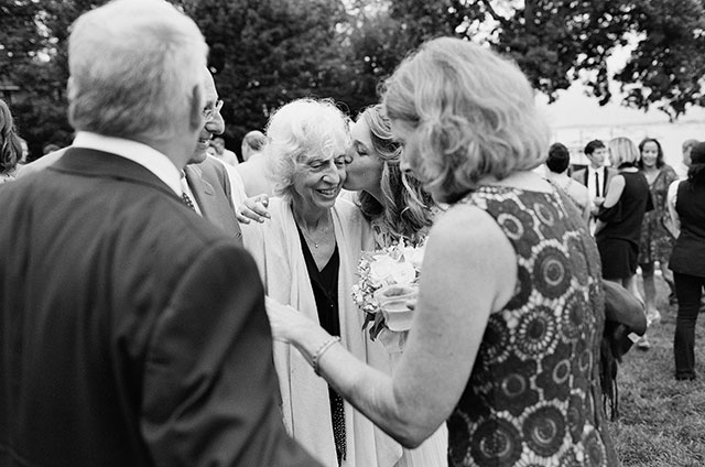 black and white film photo of bride kissing mother in law - Sarah Der Photography