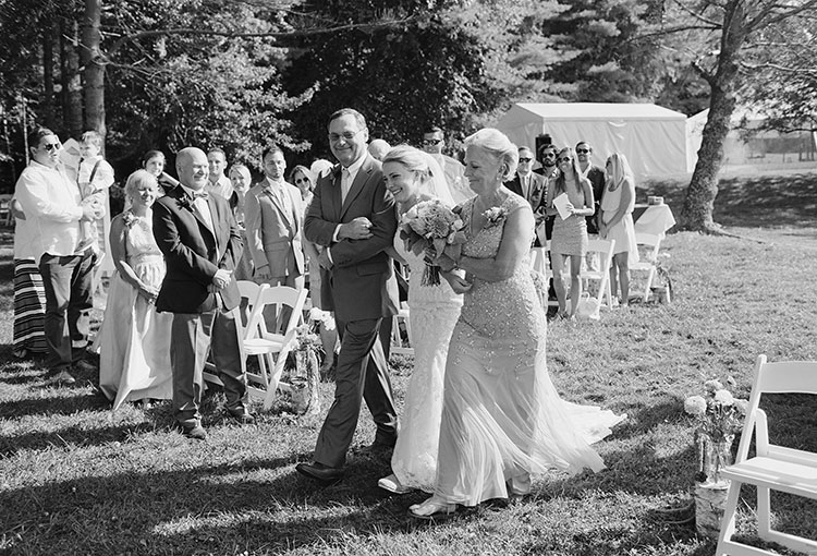 black and white film image of bride walking down aisle with both parents - Sarah Der Photography