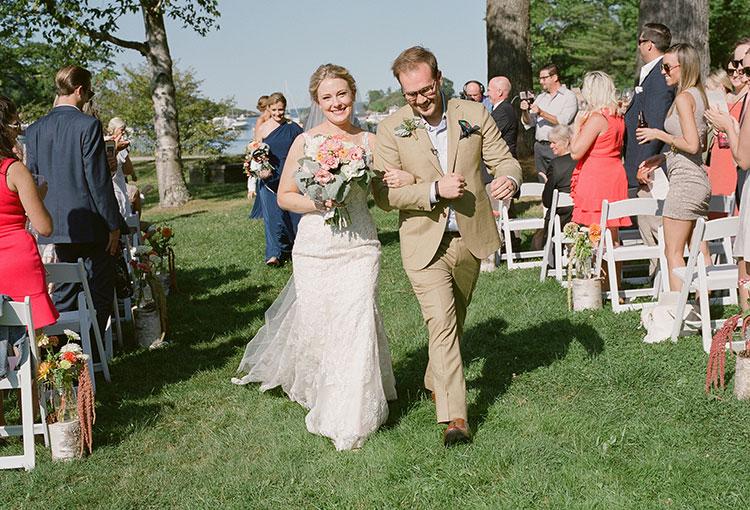 couple walks joyfully down aisle as husband and wife - Sarah Der Photography