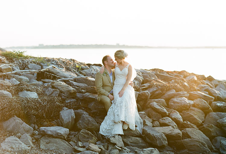 backlit portrait shot on film of couple sitting on rocks in the bay - Sarah Der Photography