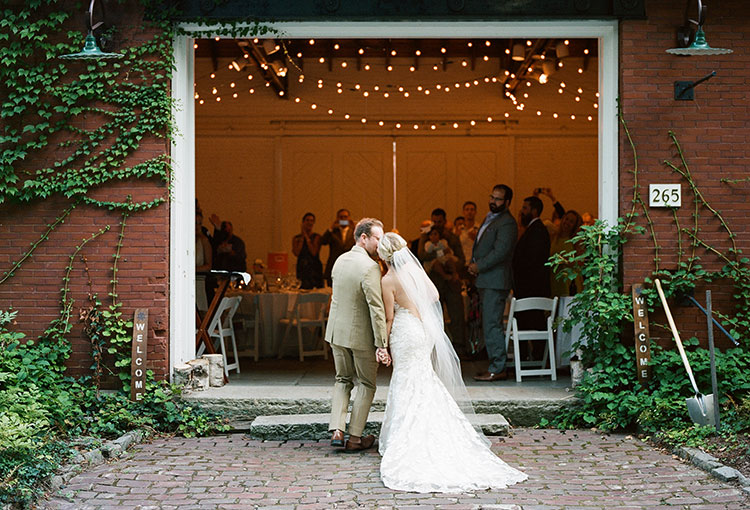 bride kisses outside barn before entering as husband and wife - Sarah Der Photography