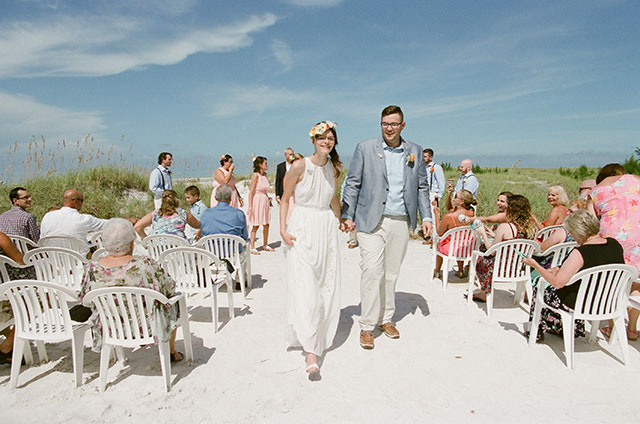 wedding image of bride and groom walking down aisle on the beach