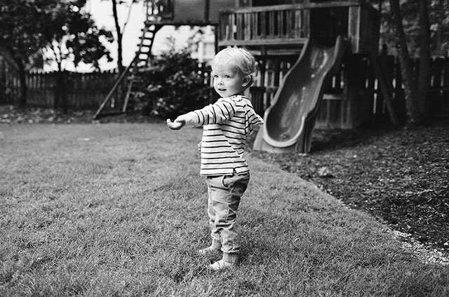 black and white 35mm photo of child playing with rocks
