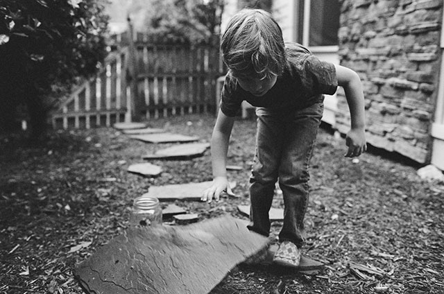 black and white image of boy looking for potato bugs