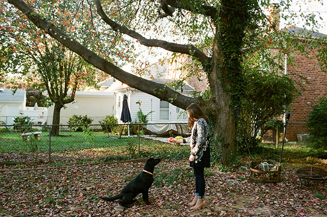 backyard photo of couple with black lab dog