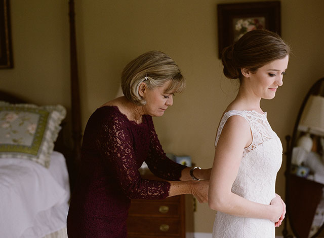 mom buttons bride up in dress
