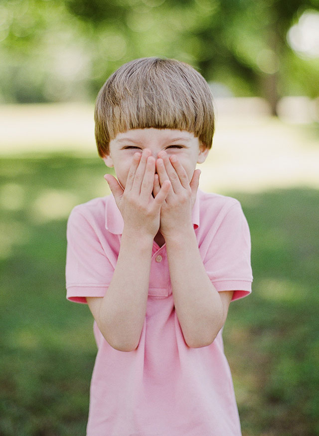 Candid and sweet film family photography image of boy laughing and covering his mouth with his hands.