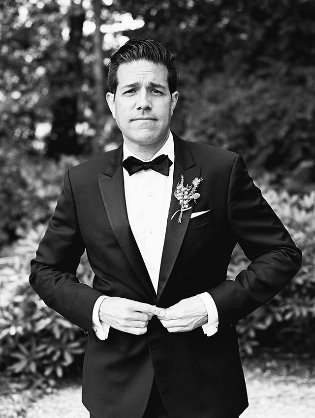 black and white film portrait of groom buttoning up his suit jacket.
