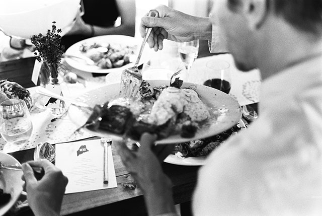 black and white photo of guest serving himself food at reception at marianmade barn.