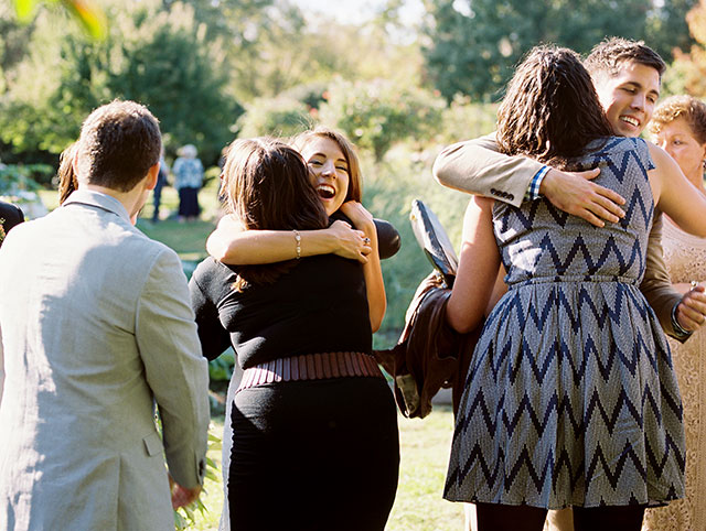 Bride hugs guests at receiving line following ceremony and she is smiling