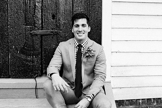 35mm black and white portrait of groom sitting on steps, smiling