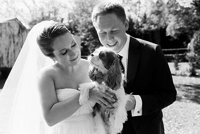 Couple takes portraits with their dog on their wedding day