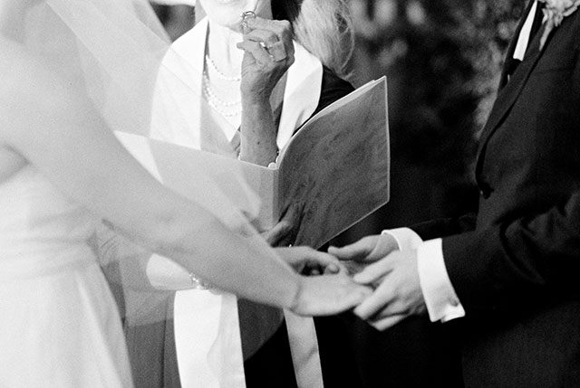 Black and white photo of couple about to exchange wedding rings