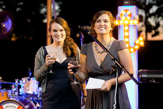 Image of sisters of the bride giving toasts with nautical light in background