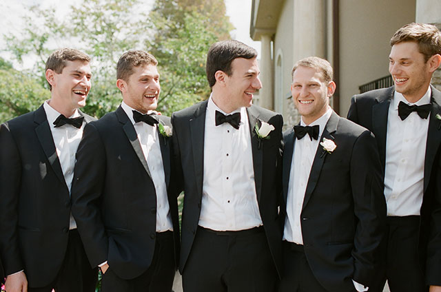 groom and groomsmen laughing in tuxes