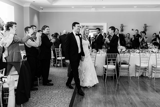 Bride and groom enter reception to applause of guests