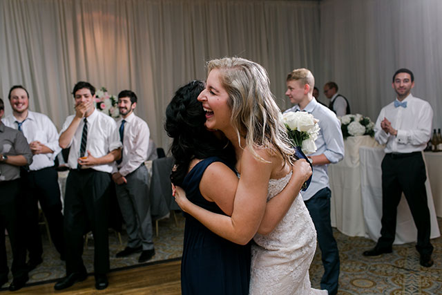 bride hugs guest who catches bouquet