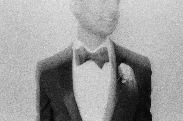 35mm black and white portrait of groom in hotel suite