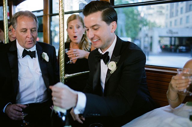Candid photo of groom popping the cork on the bottle of champagne