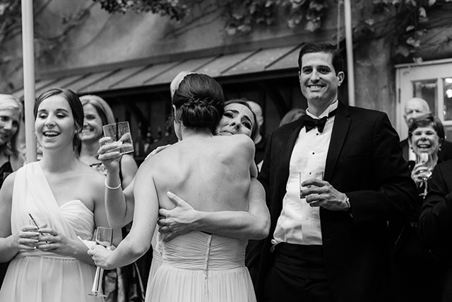 Black and white image of bride's sister hugging the maid of honor