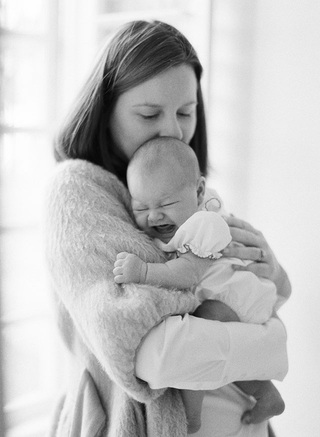 film newborn photograph shot on ilford black and white of mother holding newborn baby  by Sarah Der Photography