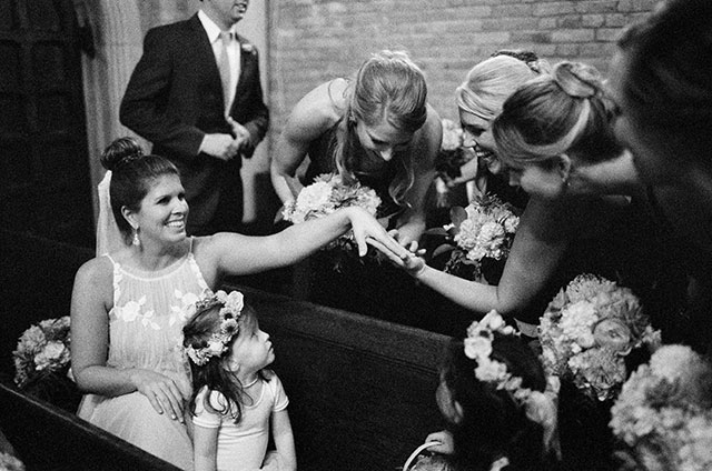 candid and sweet photo of bridesmaids admiring bride's wedding band