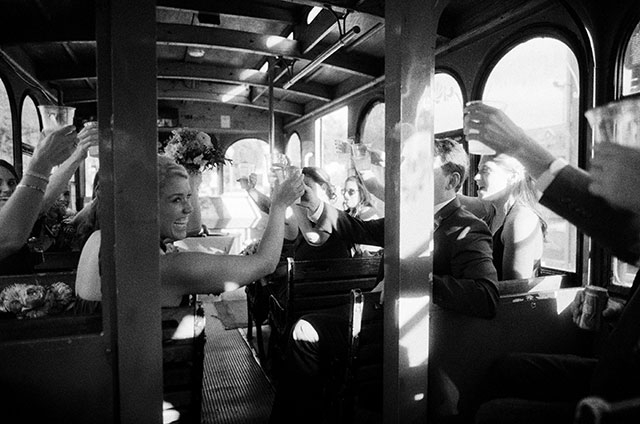 black and white shot of bridal party on trolley