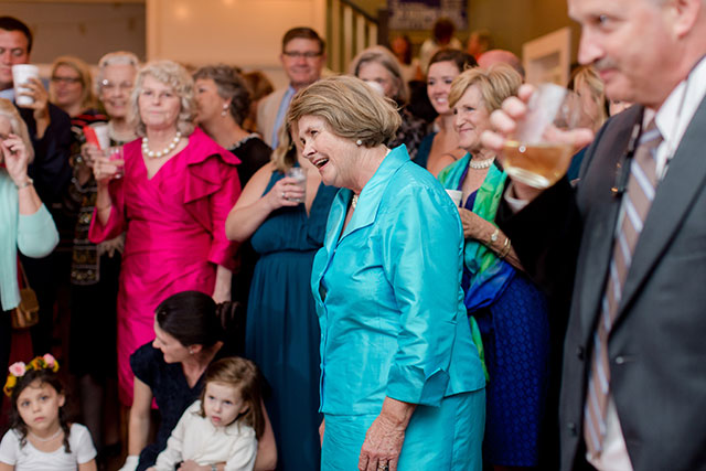 mother of the bride watching as couple cuts the cake