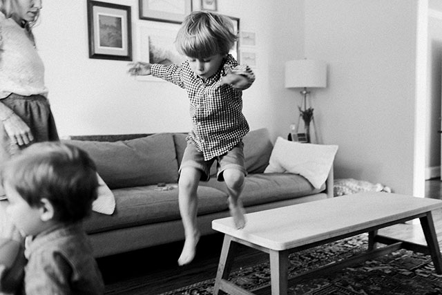 Boy jumping off coffee table, shot on black and white ilford film by Sarah Der Photography
