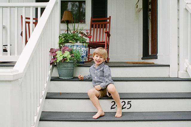Boy on front stoop of home, smiling by Arlington, VA family photography by Sarah Der Photography